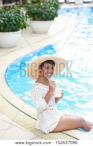 Lovely Indonesian woman enjoying cocktail at spa resort