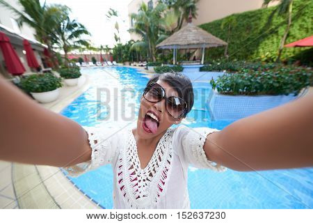 Young woman taking funny selfie by the pool