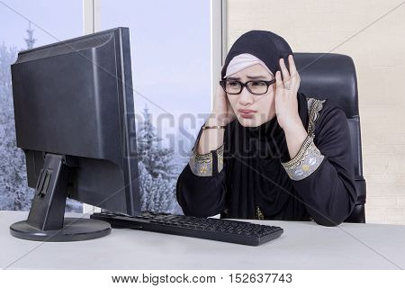Arabian entrepreneur looking at the computer while her holds head and looks frustrated with winter background on the window