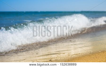 Soft wave of blue ocean on sandy beach. Background.