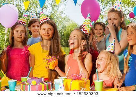 Group of happy kids congratulating excited girl at the outdoor birthday party