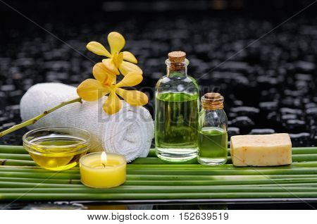 spa concept â??orchid and ,candle , oil,towel, green long leaf