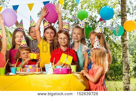 Group of happy kids in party hats congratulating birthday boy at the outdoor party