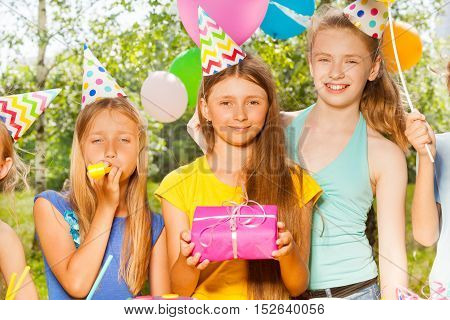Three happy girls in party hats with present and whistle at the outdoor Birthday party