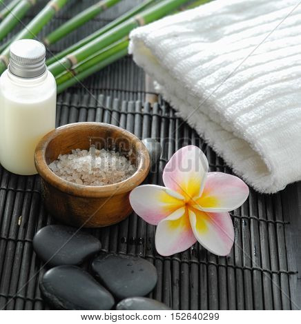 White towel and stones and oil, grove, frangipani on bamboo mat