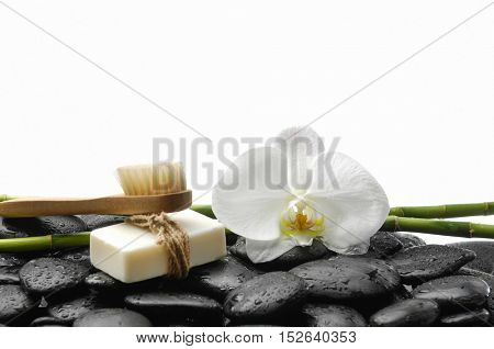 White orchid blossom with black stones ,grove,soap on wet background