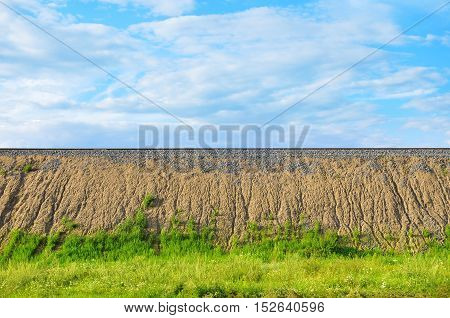 Sandy with railroad rails and green grass against the blue sky. Natural background with place for text.