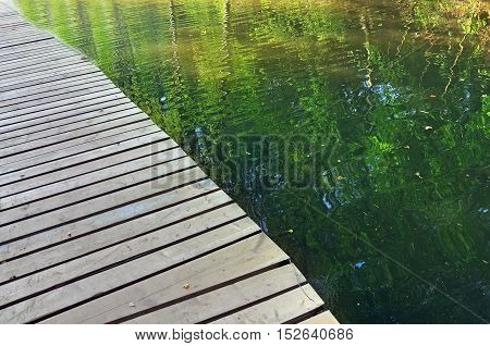 Wooden pier in perspective on a background of river surface reflecting trees.