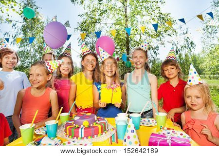 Big happy kid's company celebrating Birthday outdoor in the summer park
