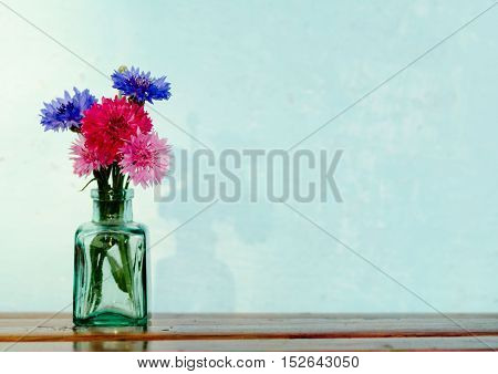 Bunch of beautiful blue red and pink cornflowers in green glass bottle.