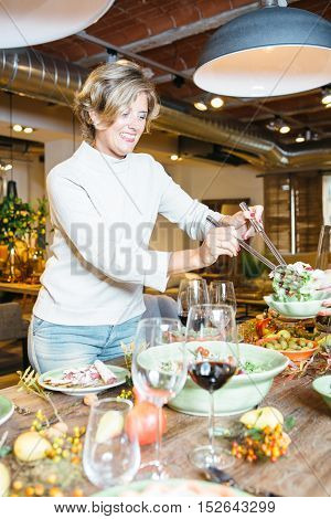 Smiling woman standing at dinner table. Side view portrait.