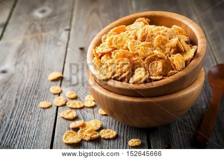 Cornflakes for breakfast in a bamboo plate on old wooden background. Selective focus.