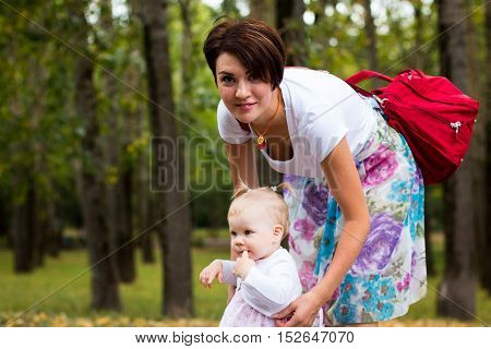 Small Cute Baby And Nice Mom Outdoors