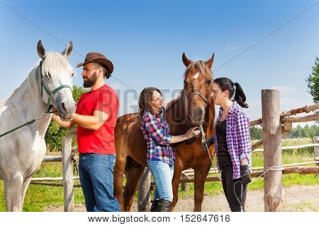 Three horseback riders having rest with their horses, standing next to the fence of the paddock at sunny day