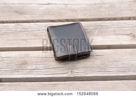 Lost leather wallet on empty wooden bench
