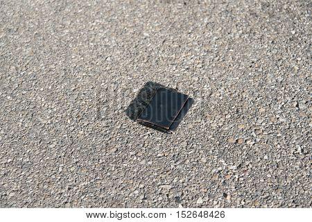 Lost leather wallet on the asphalt detail