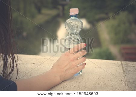 Beautiful woman hand holding a bottled water vintage view