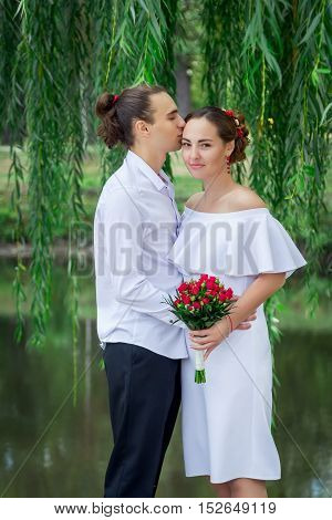 Happy loving wedding couple hugging  in the park with bouquet of red roses. Handsome young groom kissing beautiful smiling bride