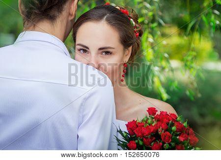 Beautiful young bride embracing her groom, happy wedding couple