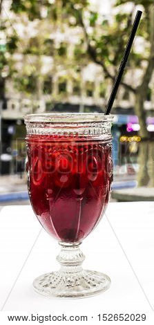 A photo of a vibrant red cocktail with a straw on a cafe terrace table, with blurred city lights in the background