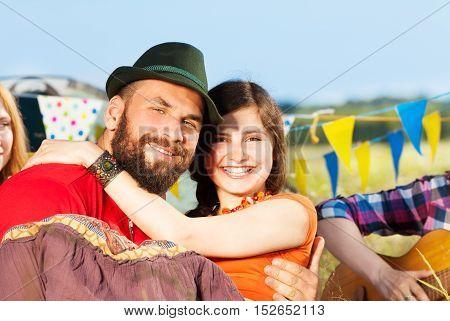 Close-up portrait of smiling man in hat holding his girlfriend