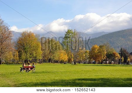Zakopane, Poland - October 9, 2014: Autumn park with vacationers people against the backdrop of mountain scenery.