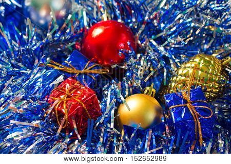Christmas ornament closeup. Red and gold ball. Golden pine. Blue and red wrapped gifts. Sparkling ribbon on background. Close-up photo for New Year greeting card seasonal holiday banner template