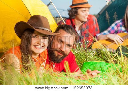 Close-up portrait of happy young couple lying on the grass next to their tent