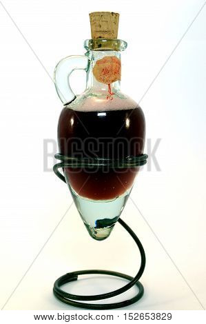 Glass amphora with some red vinegar rest on a tripod in the shape of spring.