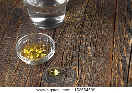 Fish oil capsules in bowl and glass water on old wooden background