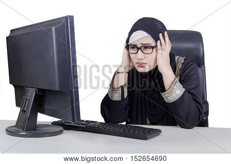 Beautiful Arabian businesswoman sitting and looking at computer while having problem with her computer isolated on the white background