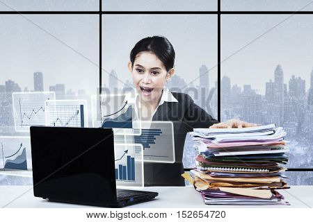 Young businesswoman sitting in front of laptop and looking virtual chart while screaming in the office with a pile of paperwork on the table