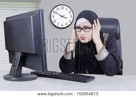 Image of beautiful Arabian businesswoman holds her head and looks frustrated with computer on the table