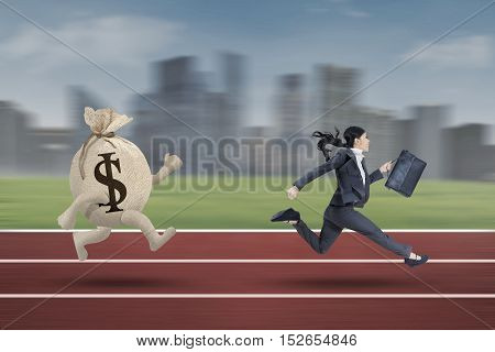 Businesswoman running with bring briefcase on the track while escaping from a bag of dollar