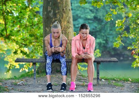 Shot Of Two Females Taking A Quick Break While Out For A Trail Run Using Phone