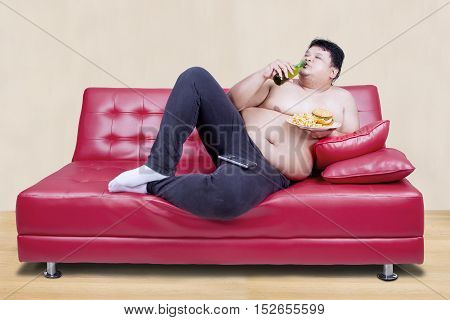 Image of fat man leaning on the couch while drinking beer and holding burger with watching tv
