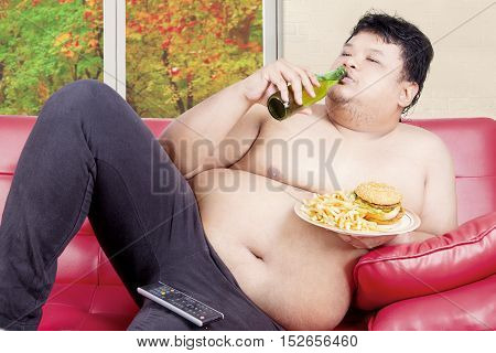 Young overweight man reclining on couch while drinking and eating junk food with autumn background on the window