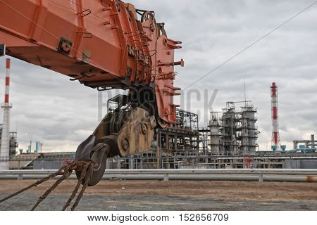 telescopic boom and a hook of the crane on background of the old refinery