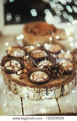 the window with the lights on a wooden table in the forms of cake and nuts