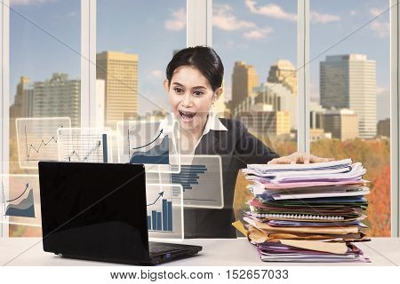 Portrait of shocked young entrepreneur looking at virtual chart on the laptop while holding a pile of document with autumn background on the window
