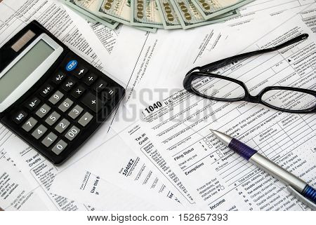 Tax form with pen glasses dollars and calculator