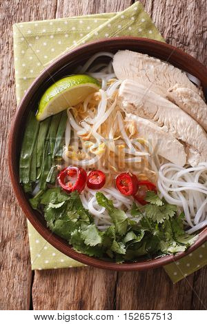 Vietnamese Food: Spicy Soup Pho Ga With Chicken, Rice Noodles And Herbs Close-up. Vertical Top View