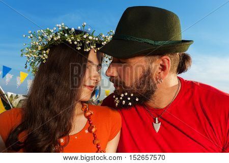 Close-up portrait of young couple, pretty woman in chamomile chaplet and man in hat, kissing against blue sky