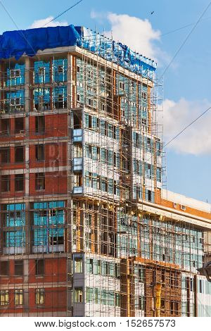 Construction of a building. A brick wall surrounded by scaffolding.