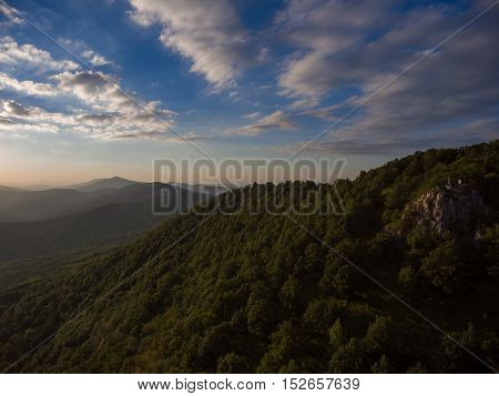 Rock Covered With Forest And Cloudy Dramatic Sky.