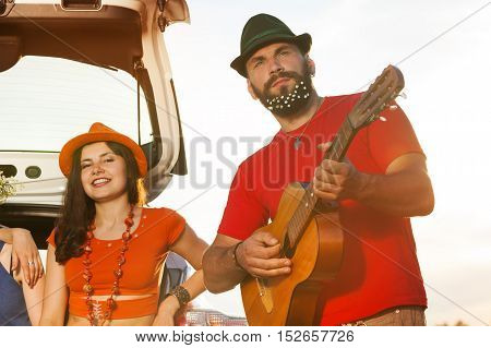 Portrait of romantic young man playing guitar for beautiful girl, sitting in a car boot