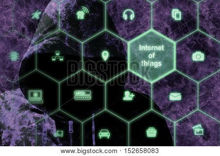 Dark hacker behind a hexagon network with symbols of the internet of things cybersecurity concept