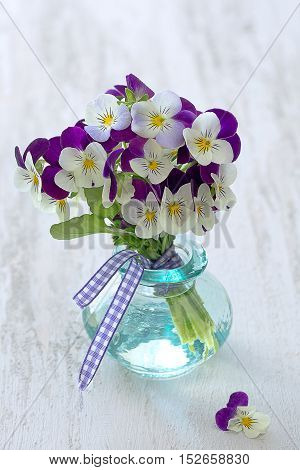 Photo of a beautiful purple pansy flowers in a glass vase on a wooden table .