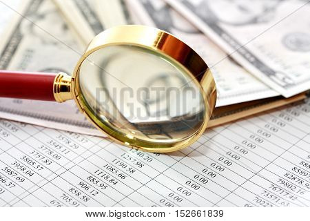 Magnifying glass near money on paper background with digits