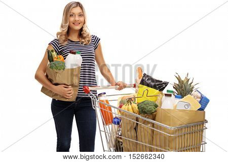 Young woman posing with a shopping bag and a shopping cart full of groceries isolated on white background